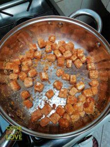 Tofu cooking in pan on stovetop