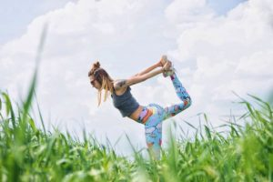 Woman in yoga pose in a field.