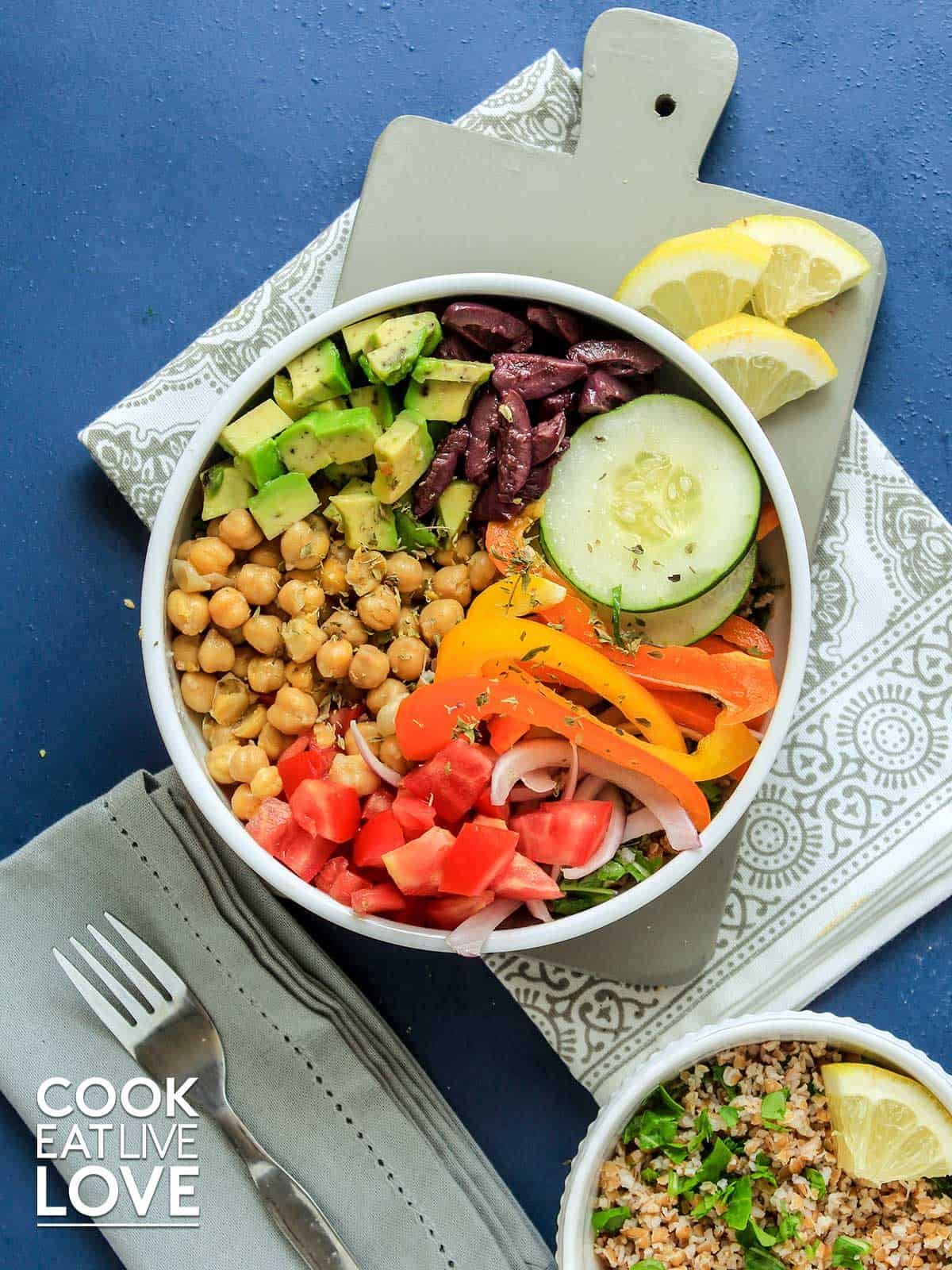 Mediterranean grain bowl on the table with fresh lmeon slices