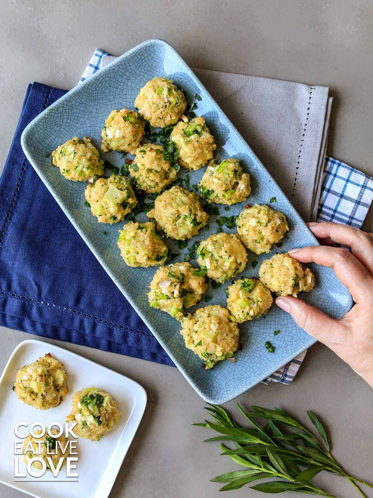 Broccoli quinoa bites on a platter with hand reaching to grab one