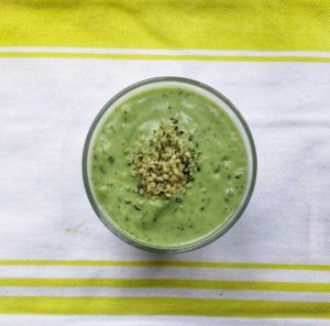 Green smoothie with spinach pictured in glass on tea towel. Garnished with hemp seeds.