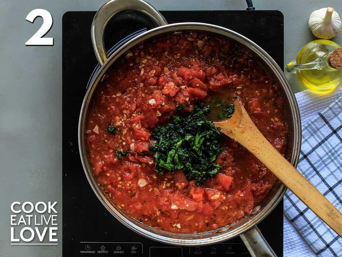 Fresh basil added to the pot of hearty marinara sauce