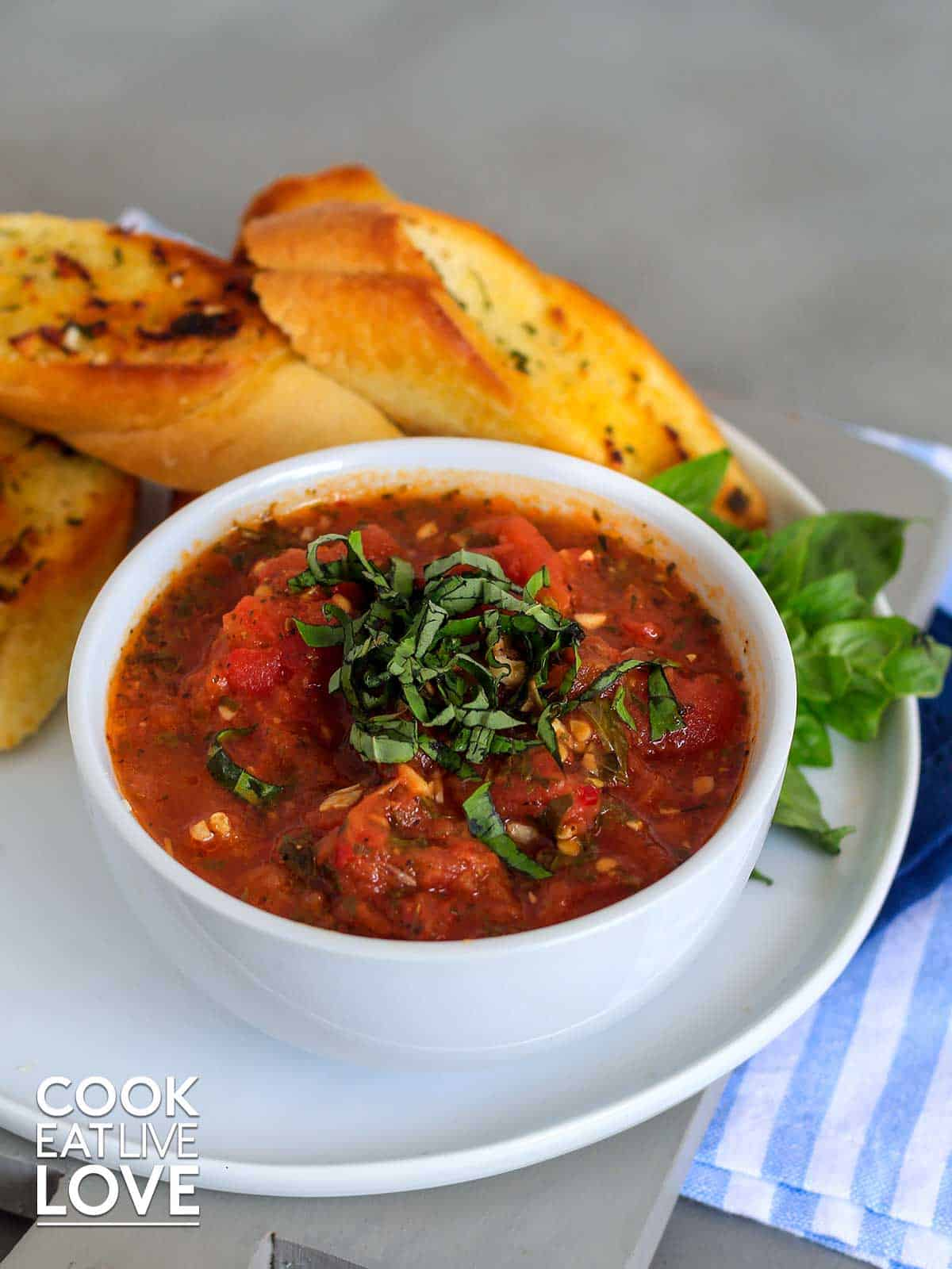 Hearty tomato sauce in bowl on a table with garlic bread