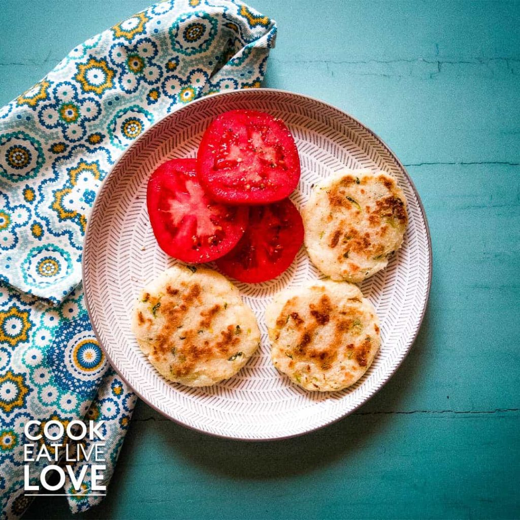 arepas with zucchini on white plate and blue background