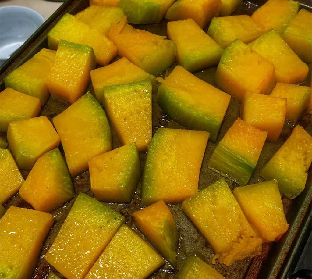 squash cut up, tossed in oil and on a pan to cook before being pureed to use in quinotto.