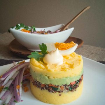 Layered causa on white plate with salsa criolla on side.