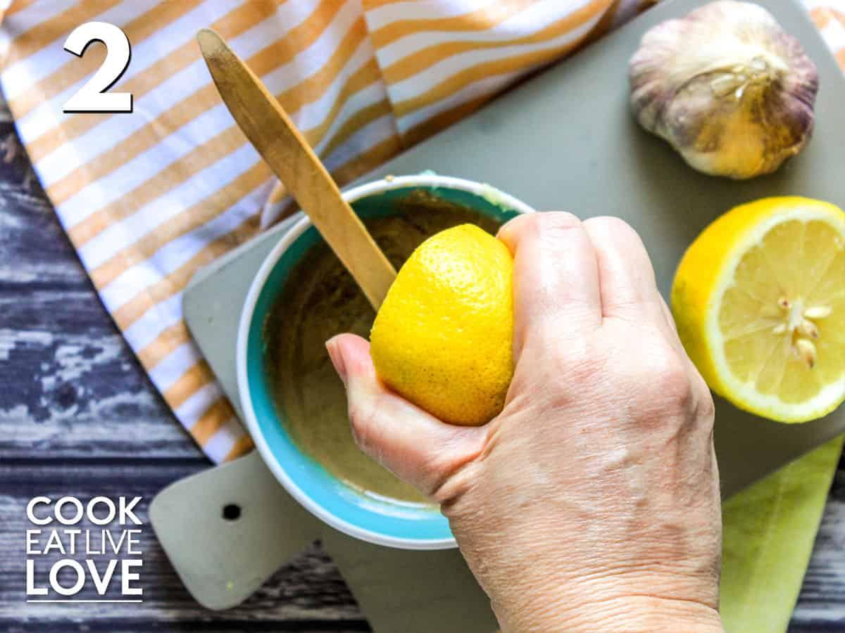 Squeezing lemon into tahini sauce