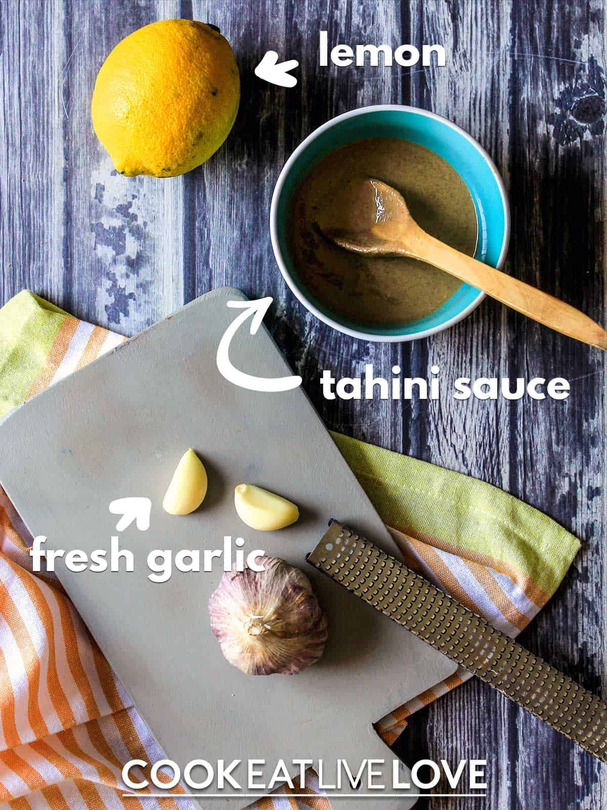 Ingredients to make vegan tahini dressing on table with text
