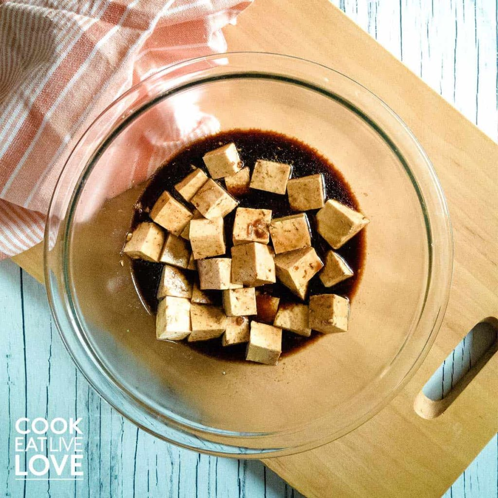 Tofu and marinade in glass bowl