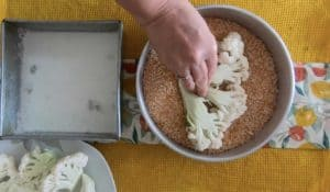 Step 2 - Dipping the cauliflower in breadcrumb mixture.
