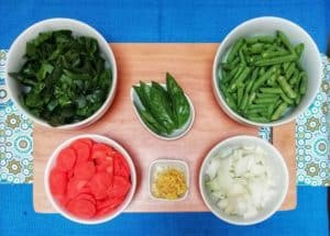 Vegetable ingredients for the recipe are in white bowls on a wooden cutting board and blue linen.