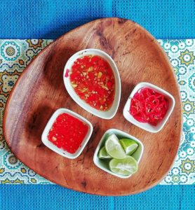 Condiments are crucial to Thai Food. Pictured here are limes, diced peppers, Nam Prik, chilies in rice wine vinegar