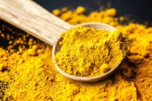 Ground turmeric pictured spilling from wooden measuring spoon