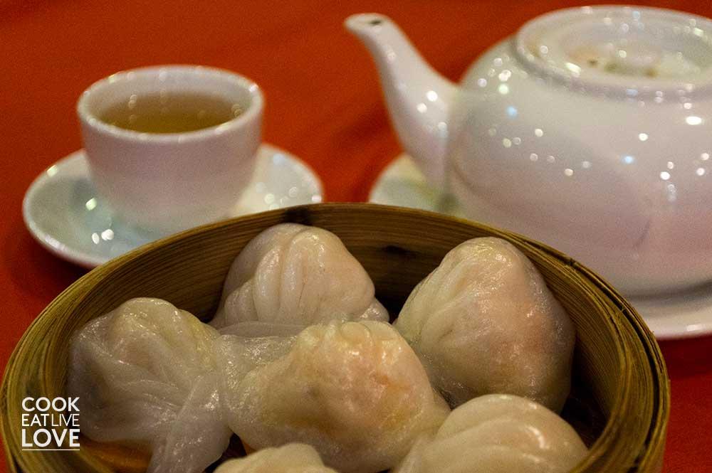 Steamed shrimp shumai, cup of hot tea and tea pot.
