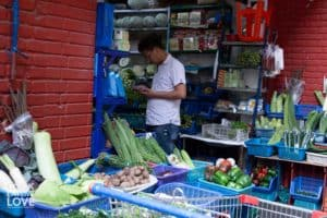 Man standing in doorway of vegetable market. On display are a variety of fresh vegetables available for purchase.