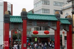 Red and green gated entrance to Barrio Chino. Green tile roof with red pillars and hanging shiny red Chinese globes.