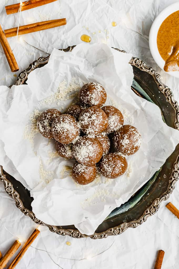 Gingerbread energy balls on a plate with powdered sugar