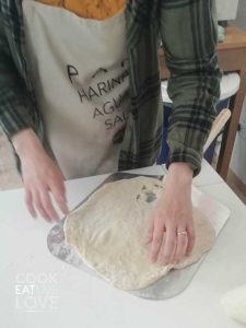Transferring the pizza to oven with pizza paddle.