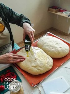 Drizzling the focaccia dough with olive oil