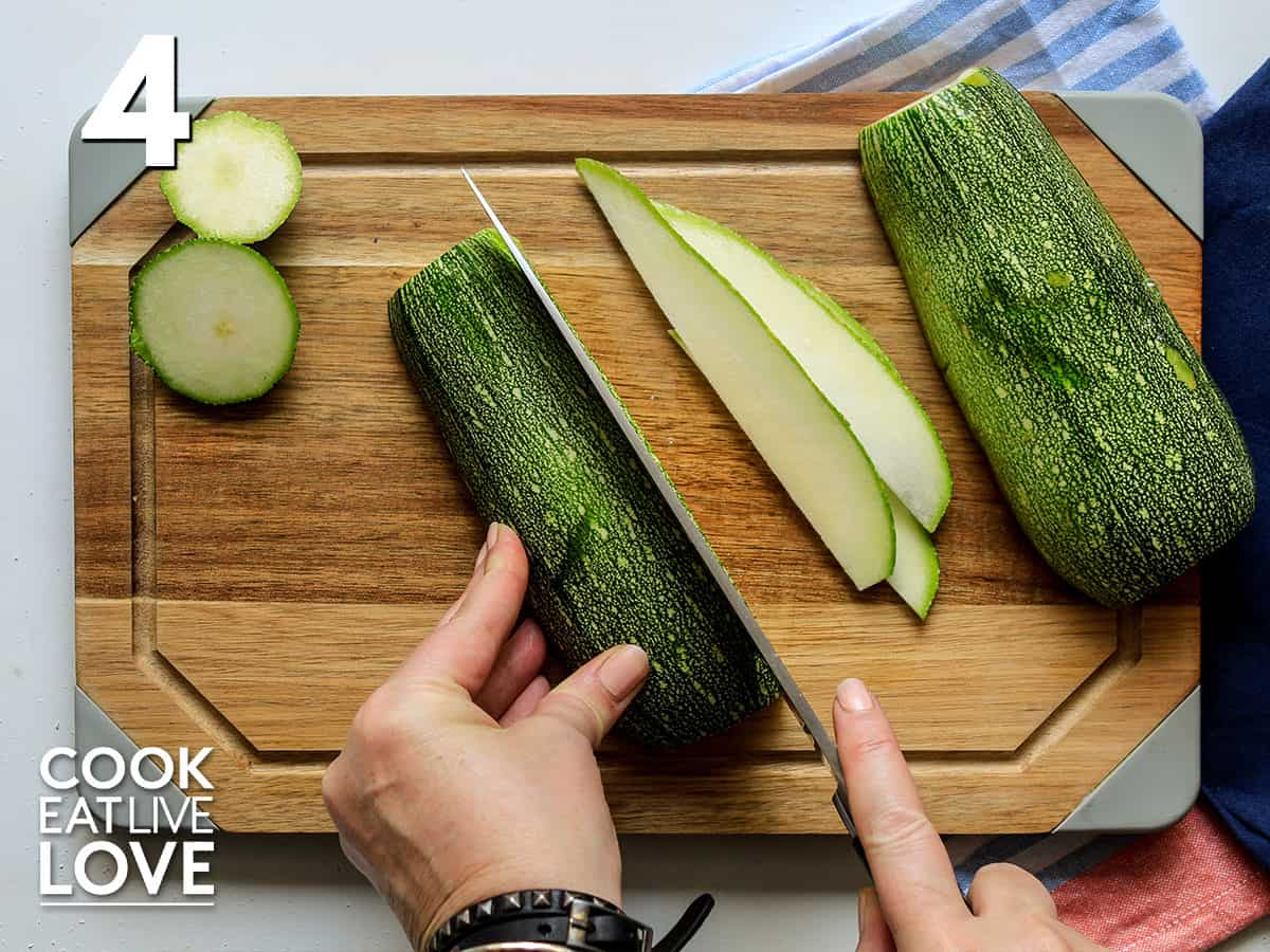 Slicing the halved zucchini into thin slices on a cutting board