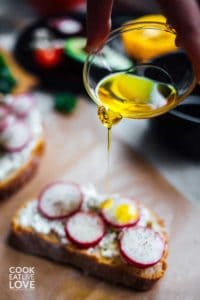 Olive oil, a healthy fat part of healthy dieting, drizzling over sandwich.