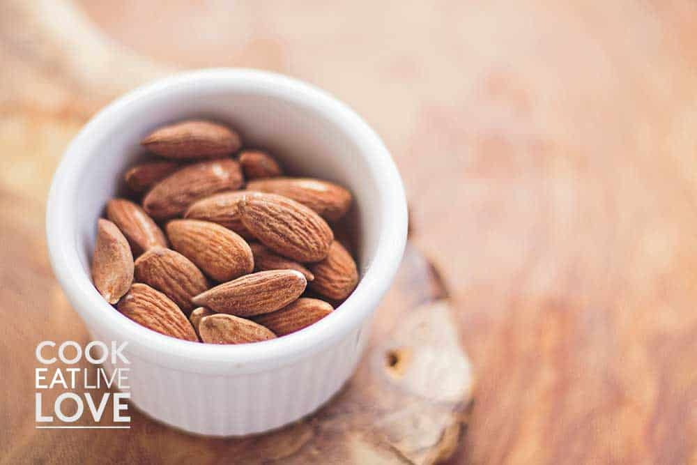 Almonds in ramekin on wood table