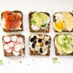 Six toasts topped with various fruit and veggie options