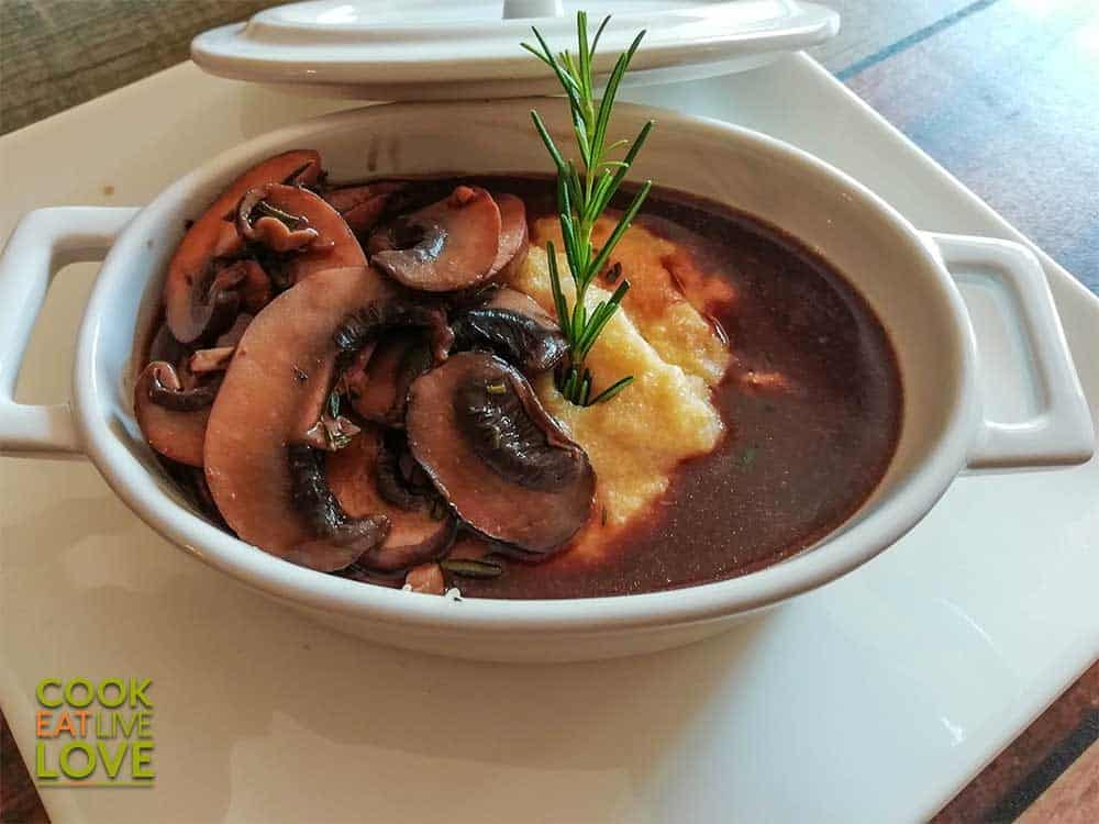 Photo of polenta with miso red wine mushroom sauce in small casserole dish on top of white plate.