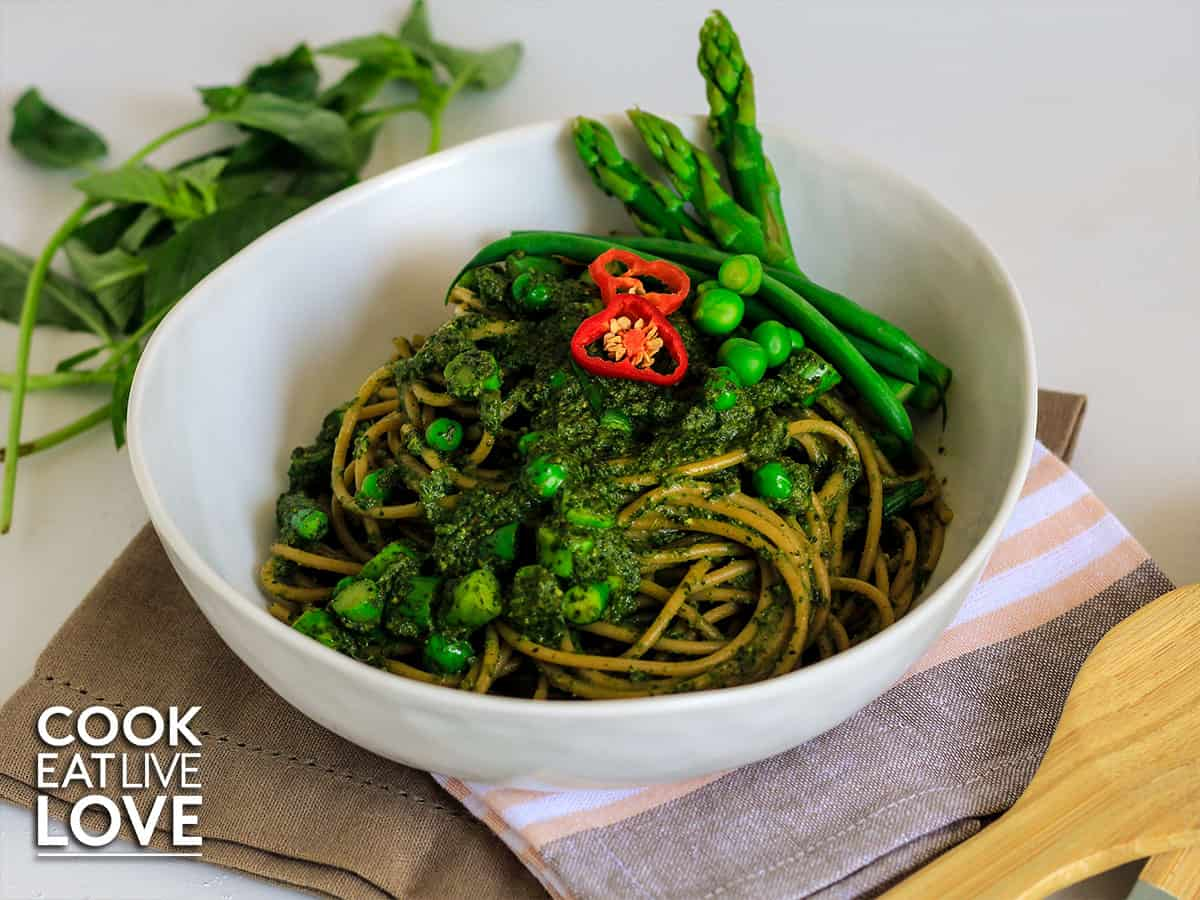 Plate of Tallarines Verdes on white background with habas, green beans and basil