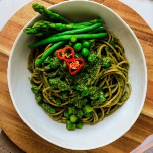 Tallarines verdes in white bowl with green beans and habas
