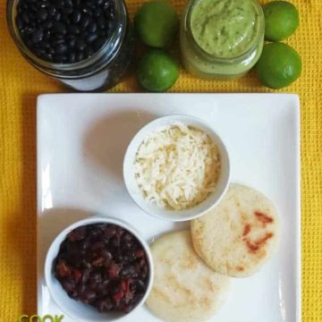 Plate of arepas with black beans and cheese.