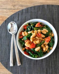Bowl of Beans and greens on gray placemat with spoons to the left of bowl.