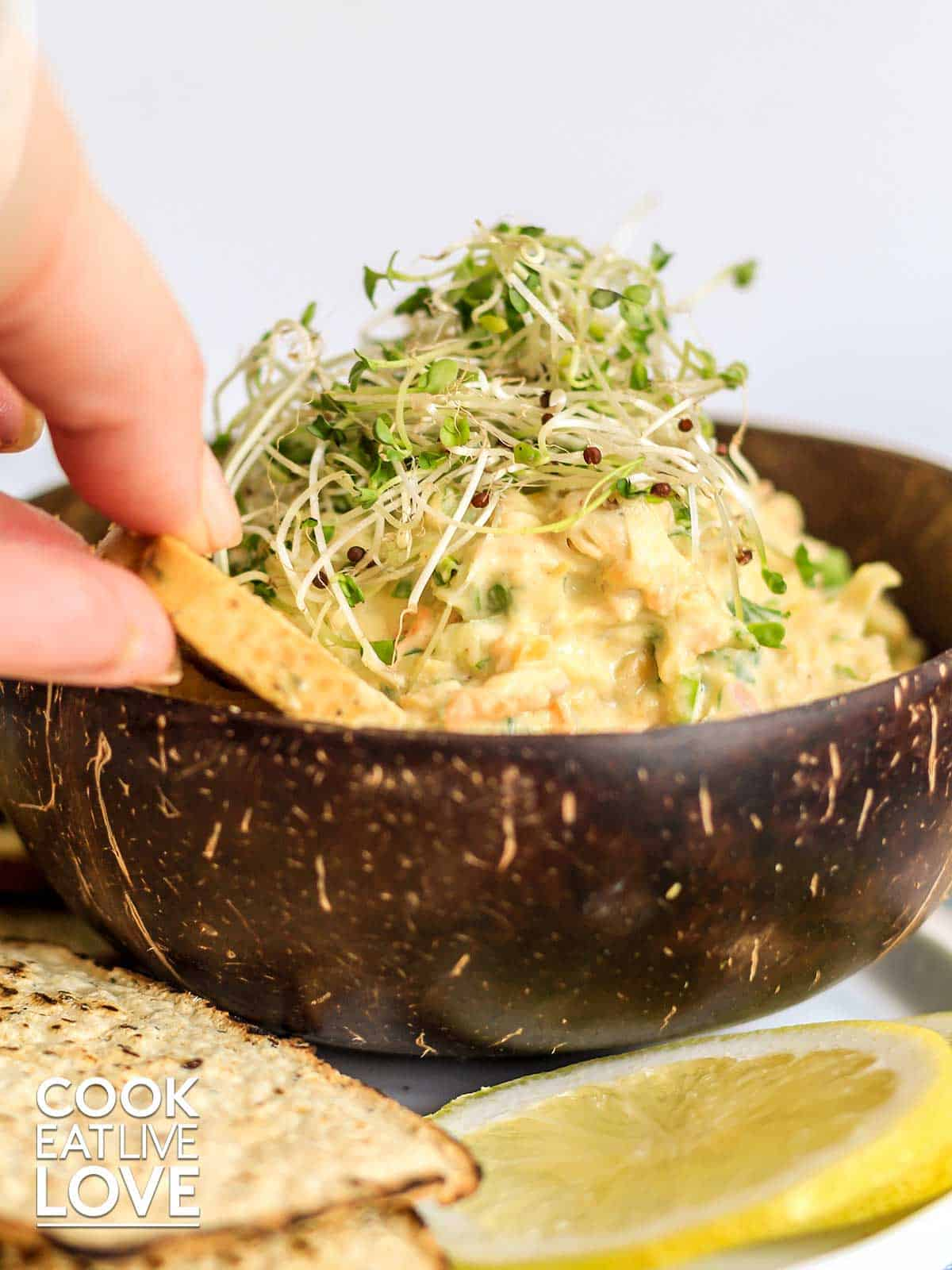 Fingers dipping a cracker into a bowl of mashed chickpea salad