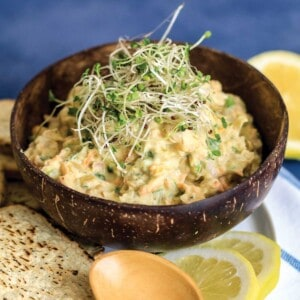 Mashed chickpea salad in a brown bowl with sprouts on top