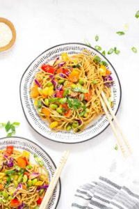 White and blue plate with noodle salad accompanied by wooden chopsticks.