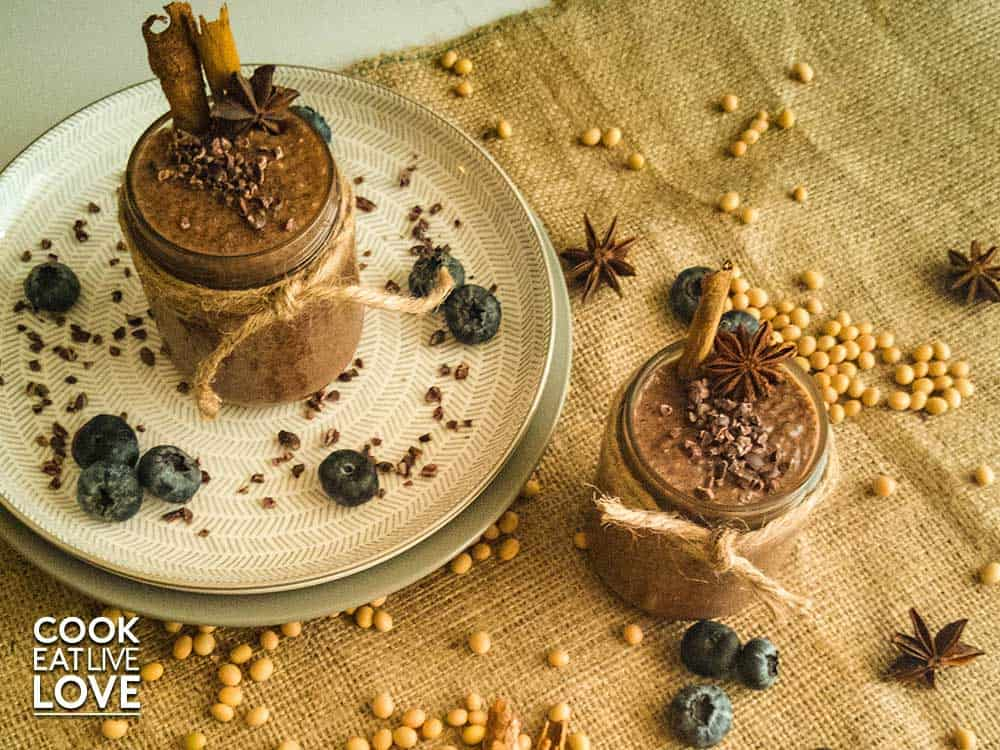 Jars of cacao chia pudding are on top of burlap, decorated with dried soybeans, cacao nibs, blueberries and whole spices.