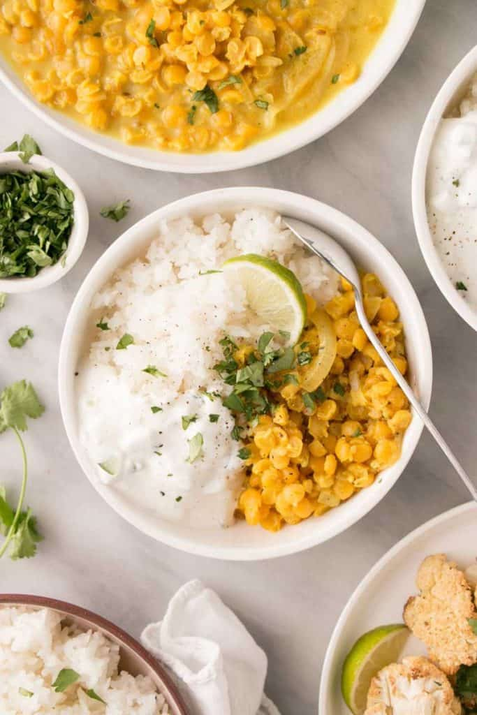 Bowl of yellow dal and white rice displayed on white background. Bowl is garnished with lime and chopped parsley.