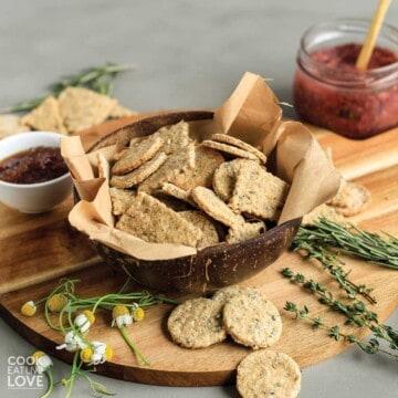 Okara crackers in a bowl on a cutting board with fresh herbs