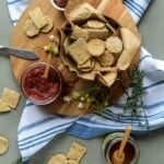 Bowl of soy crackers are garnished with sprig of rosemary and set on burlap scattered with dried soybeans.