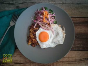 Landscape shot of finished tacu tacu topped with sunny side up egg and salsa criolla