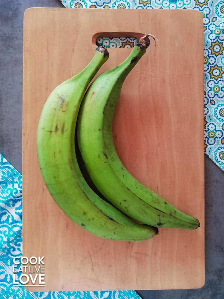 Green plantains on wood cutting board. Pictured with peel on.