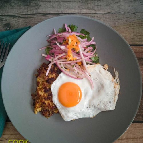 Picture of tacu tacu topped with egg and salsa criolla.