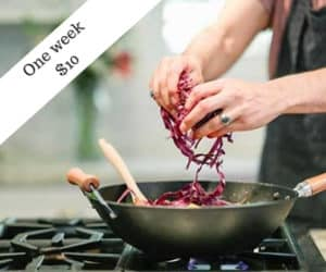 Product ad photo with person adding red cabbage to wok.
