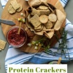 Pin for pinterest with text overlay and photo of crackers in bowl garnished with rosemary.