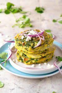 Blue plate with stack of fritters garnished with red onion