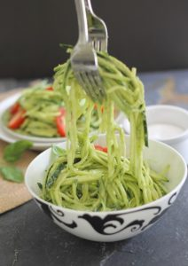 Bowl of zucchini noodles with avocado sauce. Above bowl, two forks are lifting noodles up from bowl.