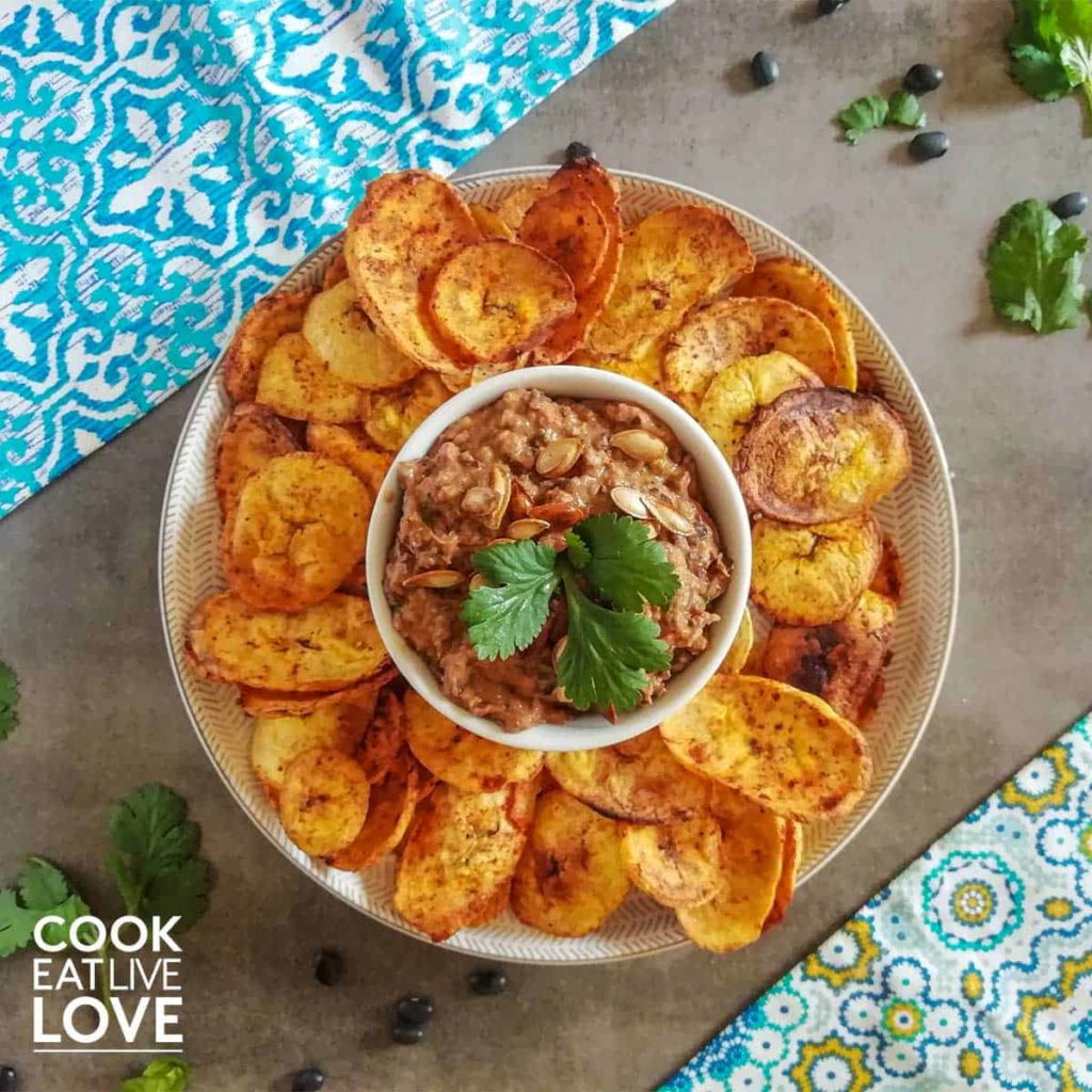 Bowl of hummus on plate with plantain chips