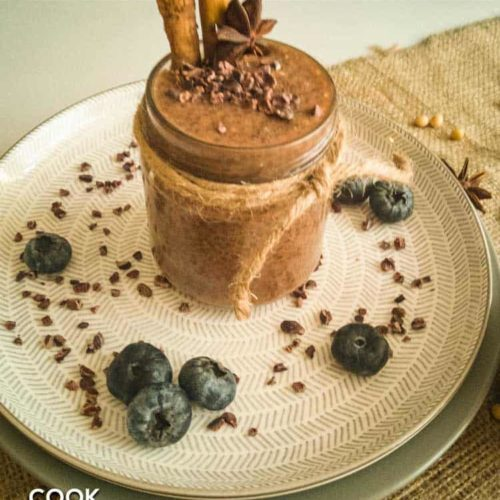 Cacao chia pudding is garnished with whole cinnamon sticks and cacao nibs on white and gray plate.