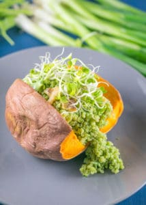 Sweet potato on matte gray plate topped with green quinoa.
