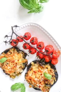 Portobello pizzas on white plate on white background. Garnished with roasted tomatoes on stem.